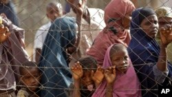 FILE - People queue outside a food distribution center as they wait to be registered as refugees in Dadaab, Kenya, Aug. 1, 2011.