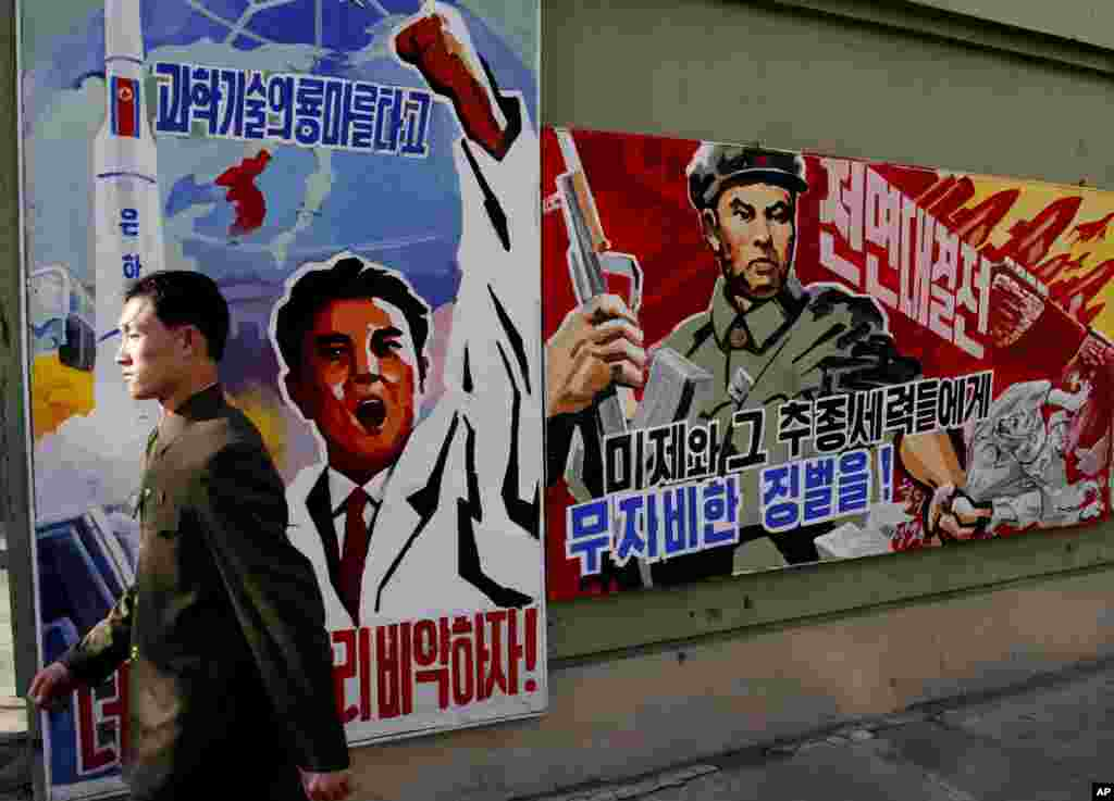 "A man walks past propaganda posters that threaten punishment to the ""U.S. imperialists and their allies,"" Pyongyang, North Korea, March 26, 2013."