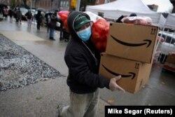Ilustrasi. Seorang pria bermasker membawa paket makanan untuk penduduk yang membutuhkan di wilayah Brooklyn di kota New York City, New York, AS, 24 April , 2020. (Foto: Reuters/Mike Segar)