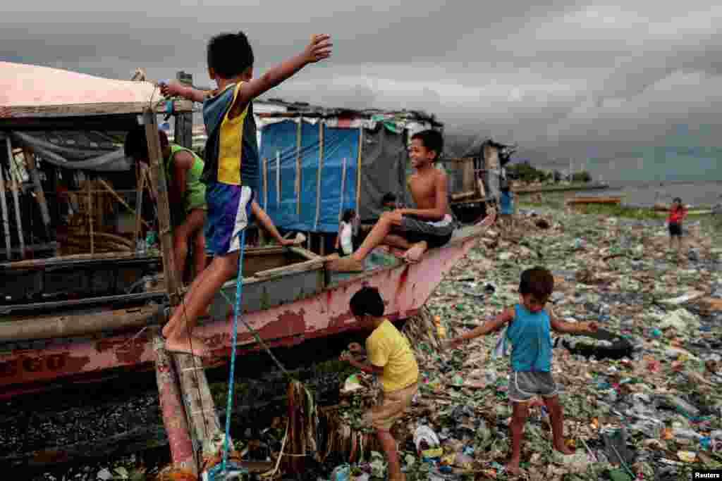 필리핀 마닐라의 쓰레기로 가득찬 바세코 해변에서 어린 아이들이 배를 놀이터삼아 놀고 있다.