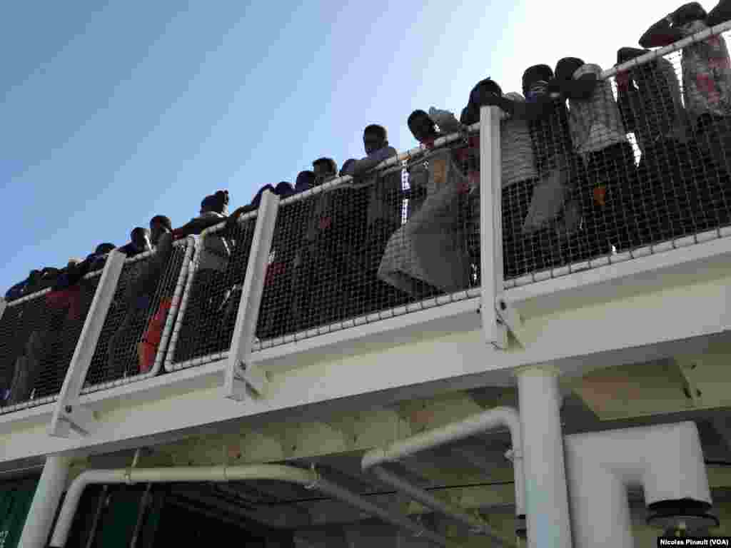 Migrants wait to disembark the Spanish vessel which rescued them in the Mediterranean, as they arrive in Pozzallo.
