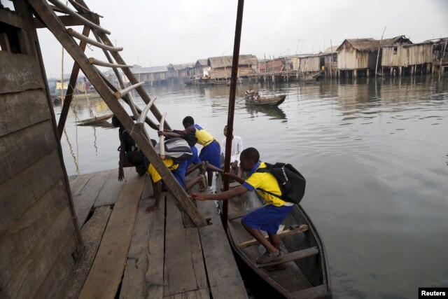 Students who attend a floating school arrive by canoe to school in the Makoko fishing community on the Lagos Lagoon, Nigeria, Feb. 29, 2016.