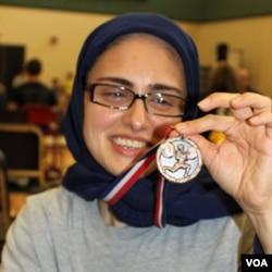 Kulsoom Abdullah menunjukkan medali yang ia menangkan dalam Kejuaraan Tingkat SMA di Georgia tahun lalu.