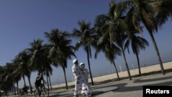 Tercio Galdino, 66, and his wife Aliceia, 65, wear their protective 'space suits' as they walk on the sidewalk of Copacabana Beach amid the outbreak of the coronavirus disease (COVID-19) in Rio de Janeiro, Brazil, July 11, 2020.