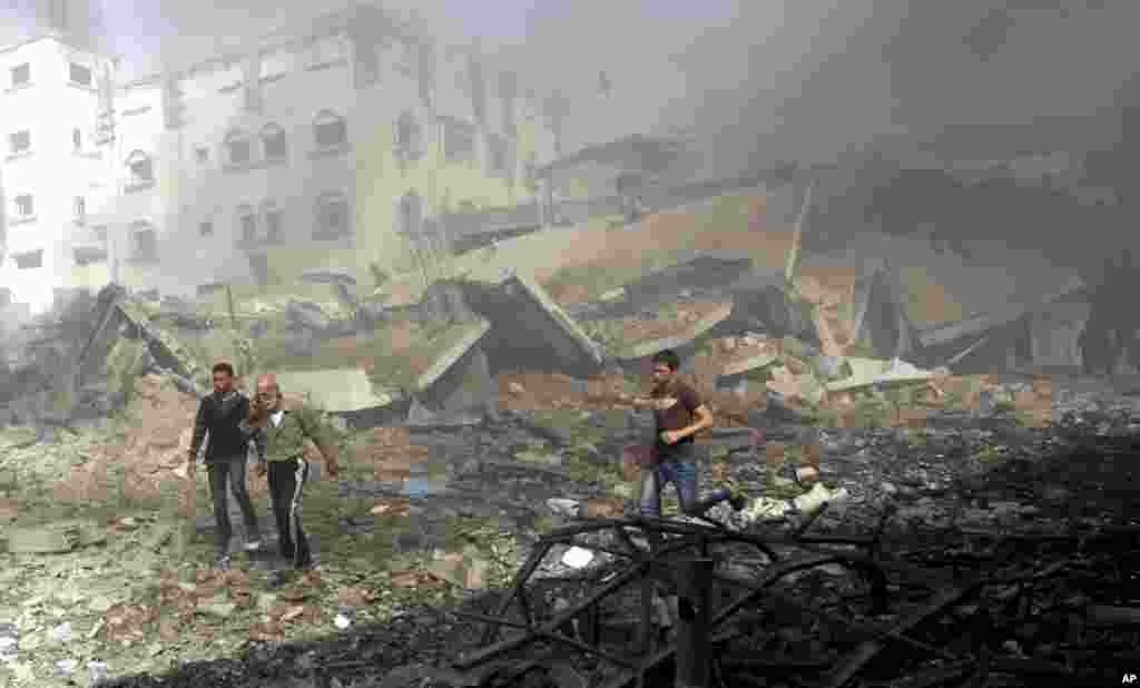 Palestinians hurry away from a damaged building after an Israeli air strike in Gaza City, November 18, 2012.