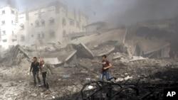 Warga Palestina memeriksa gedung yang baru dibombardir Israel di Gaza (18/11). Israel menangguhkan rencana serangan darat di tengah upaya diplomasi krisis Gaza.
