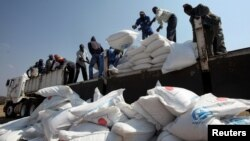 FILE: Villagers offload food aid provided by the United Nations World Food Programme (WFP) at a distribution point in Bhayu, Zimbabwe, September 14, 2016. REUTERS/Philimon Bulawayo