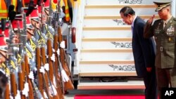 Cambodian Prime Minister Hun Sen bows to pay respects to the national flags of Cambodia and the Philippines shortly upon arrival at Clark International Airport in Clark, Pampanga province north of Manila, Philippines Saturday, Nov. 11, 2017.
