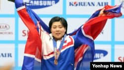 22일 달빛축제정원 역도경기장에서 열린 2014 인천 아시안게임 역도 여자 58kg급 경기 시상식에서 북한의 리정화 선수가 금메달을 목에 건 채 관중들의 답례에 환호하고 있다.