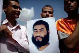 A relative of a Yemeni inmate at Guantanamo Bay holds up his poster during a protest by relatives of detainees to demand their release, outside the U.S. embassy in Sanaa April 1, 2013.
