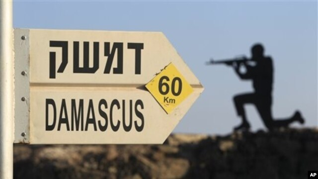 Sign showing distances to Damascus and a cut out of a soldier are seen at an army post from the 1967 war at Mt. Bental, Golan Heights, July 24, 2012.