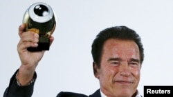 Austrian-born actor Arnold Schwarzenegger displays his Golden Icon Award during the award ceremony at the Zurich Film Festival in Zurich, Switzerland, Sept. 30, 2015.