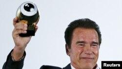 Austrian-born actor Arnold Schwarzenegger displays his Golden Icon Award during the award ceremony at the Zurich Film Festival in Zurich, Switzerland, Sept. 30, 2015.