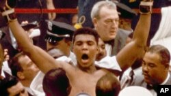 "Muhammad Ali strikes a familiar pose as he shouts ""I am the greatest,"" as he leaves the ring, arms raised, following his defeat of former heavyweight boxing champion Sonny Liston in Miami Beach, Fla., February 25, 1964."