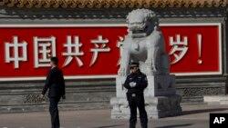 """Kineski policajci u civilu i uniformi ispred panoa na kome piše """"Živela Kineska komunistička partija"""""""