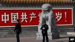 警察和便衣守在共產黨萬歲的巨幅標語牆前。(2013年11月7日)