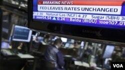 Una pantalla en la Bolsa de Nueva York muestra la decisión de la FED de dejar invariable la tasa de interés.