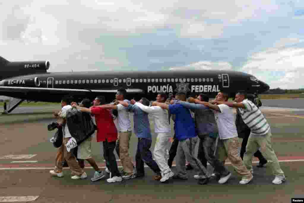 پليس فدرال گروهی از زندانيان را به سمت هواپيمای عازم محل نامعلومی در فرودگاه بین المللی موریلیا حرکت می دهند. مکزيک - بيست و يکم اوت ۲۰۱۲. رويترز