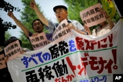 Protesters shout slogans against a Japanese nuclear plant that won preliminary approval for meeting stringent post-Fukushima safety requirements, near the Diet building in Tokyo, July 16, 2014.