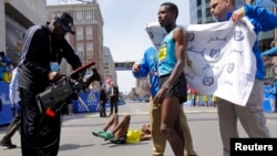"Winner of the men's division Lelisa Desisa Benti of Ethiopia (R) is wrapped in a towel as third place finisher compatriot Gebregziabher ""Gebre"" Gebremariam (C) lays on the ground during the 117th Boston Marathon in Boston, Massachusetts April 15, 2013. RE"