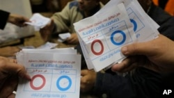"Election workers count ballots ticked ""agree"", at the end of the second, final day of a key referendum on a new constitution, inside a polling station in Cairo, Egypt, Wednesday, Jan. 15, 2014. The vote is a milestone in a military-backed political roadma"