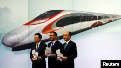Secretary for Security John Lee, from left, Secretary for Justice Rimsky Yuen and Secretary for Transport & Housing Frank Chan pose at a news conference on arrangements at West Kowloon Terminus for the Guangzhou-Shenzhen-Hong Kong Express Rail Link in Kong, July 25, 2017.