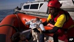 Un bébé de deux mois, en provenance de Libye, est retiré d'un navire de la Garde côtière libyenne et embarqué dans canot pneumatique de l'ONG espagnole Proactiva Open Arms, après avoir été sauvé d'une barque en bois hors de contrôle en Méditerranée, à env