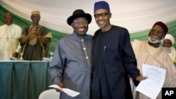 "FILE - Nigeria's President Goodluck Jonathan, center-left, and opposition candidate Gen. Muhammadu Buhari, center-right, hug and shake hands after signing a renewal of their pledge to hold peaceful ""free, fair, and credible"" elections, at a hotel in the capital Abuja, March 26, 2015."