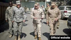 Petinggi militer AS, Jenderal Martin Dempsey (kedua dari kiri) melakukan peninjauan di Afghanistan. Pesawat Jenderal Dempsey terkena serangan roket Taliban hari Selasa (21/8).