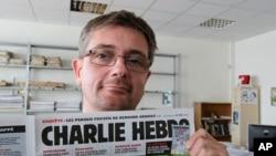 讽刺漫画刊物《查理周刊》发行总监在巴黎展示期刊头版,(2012年9月19日资料图)
