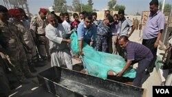 Warga Irak sedang mengurus jenazah korban tewas akibat serangan hari Selasa (13/9).