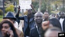 """Un homme brandit une affiche mentionnant """"Non non à l'esclavage"""" au cours d'une marche contre """"l'esclavage en Libye"""", Paris, 18 novembre 2017."""
