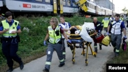 Swiss rescue workers wheel a wounded person on a stretcher after two regional trains crashed head on near Granges-Pres-Marnand near Payerne in western Switzerland, July 29, 2013.