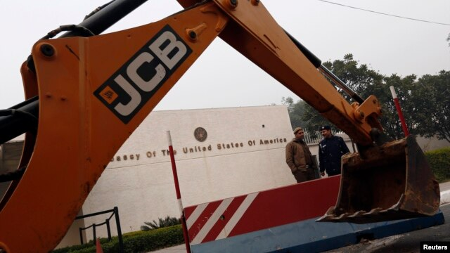 Policemen stand next to a bulldozer removing the security barriers in front of the U.S. embassy in New Delhi on December 17, 2013.
