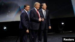 FILE - Republican presidential candidate Donald Trump is introduced by National Rifle Association executive director Chris W. Cox (L) and NRA executive vice president Wayne LaPierre (R), as Trump takes the stage to speak at the NRA convention, May 20, 201