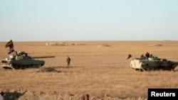 Kendaraan lapis baja mengambil posisi di tengah gurun dekat perbatasan Suriah, Irak, dalam gambar yang diambil dari video yang diperoleh Reuters, 23 November 2017. (Hashid Shaabi / Handout via Reuters TV)