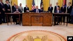 Predsednik SAD Donald Tramp govori nakon ceremonije potpisivanja sporazuma sa predsednikom Srbije Aleksandrom Vučićem (levo) i premijerom Kosova Avdulahom Hotijem, u Ovalnom kabinetu, u Beloj kući, 4. septembra 2020. (AP Photo/Evan Vucci)