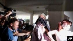 Polisi mengawal seorang wanita Inggris berusia 19 tahun (kedua dari kanan,) keluar dari pengadilan Famagusta, kota Paralimni, Siprus, Senin, 29 Juli 2019.