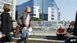 """Ljudi šetaju pored transparenta """"ne merama štednje"""" ispred zgrade Evropskog saveta u Briselu (arhivski snimak, mart 2012.)"""