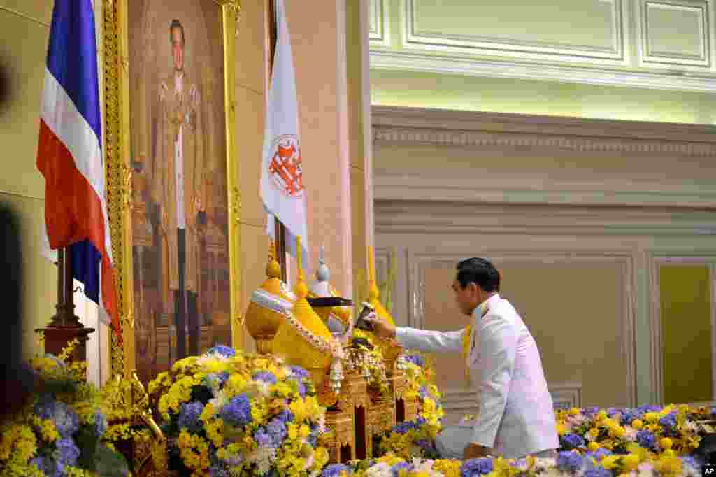 Gen. Prayuth Chan-ocha opens a container before he accepts a royal endorsement certifying his appointment as the country's 29th premier, in front of the portrait of King Bhumibol Adulyadej in Bangkok, Aug. 25, 2014.