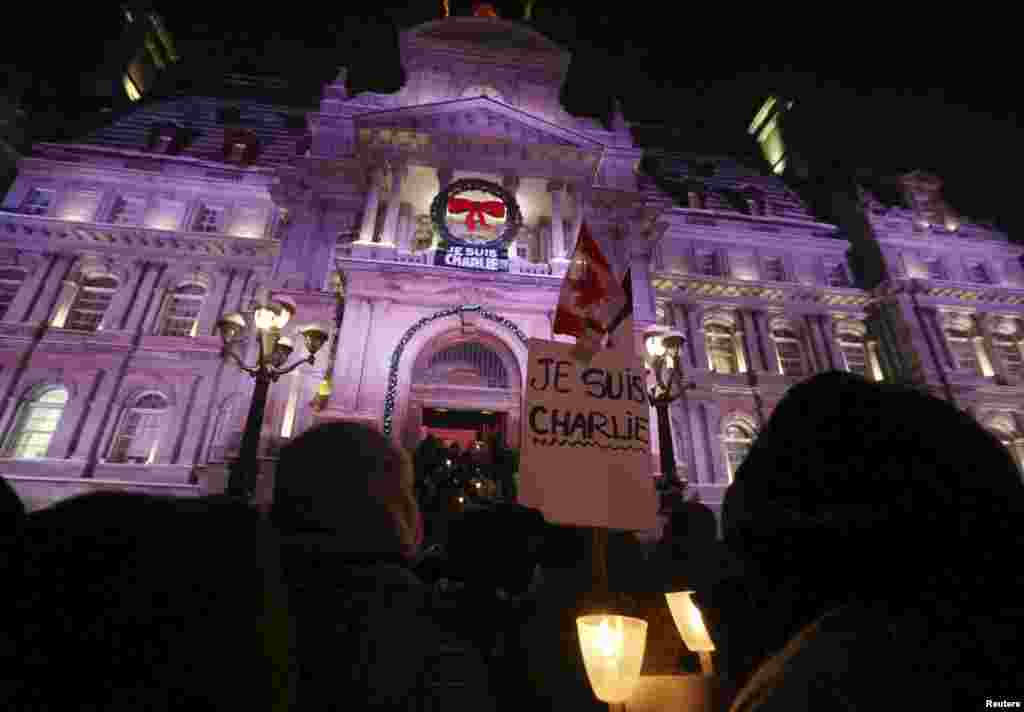 People participate in a vigil to pay tribute to the victims of a shooting, by gunmen at the offices of weekly satirical magazine Charlie Hebdo in Paris, in front of City Hall in downtown Montreal, Jan. 7, 2015.