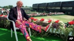 FILE - Tennis commentator Bud Collins, known for his flashy attire, displays a pair of brightly colored trousers as he sits overlooking the outside courts at Wimbledon, England, June 30, 1993. Collins died Friday at his home in Massachusetts; he was 86.