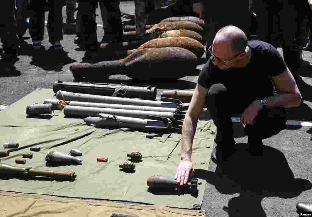Prime Minister Arseny Yatseniuk inspects weapons seized from pro-Russian separatists as he meets with Ukrainian servicemen, Slovyansk, July 16, 2014.