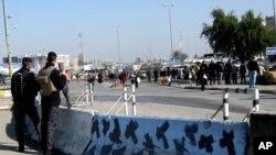 Pasukan penjaga keamanan Irak berjaga-jaga di tempat terjadinya serangan bom di Baghdad, Minggu 12 Januari 2014.