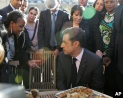 FILE - French President Nicolas Sarkozy, right, listens to representatives of French suburbs after he unveiled the much-awaited, far-reaching plan for reinvigorating suburban housing projects and integrating their young people, Feb. 8, 2008 at the Elysee Palace in Paris.