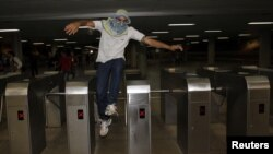 A protester jumps over a subway turnstile during a protest demanding improvements be made to the public transport system, at the bus station in the centre of Brasilia, June 19, 2013.