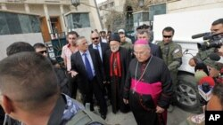 Iraqi Christian lawmaker, Younadem Kana, center left, Iraq's top Catholic prelate, Chaldean Cardinal Emmanuel III Delly, center, and Bishop Shlimone Wardoni, center right, are seen outside Our Lady of Deliverance church the morning after its congregation