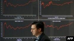 Seorang pria melewati papan indeks bursa saham di Athena, Yunani (foto: dok). Krisis Yunani mengimbas harga saham dunia yang anjlok hari Senin (29/6).