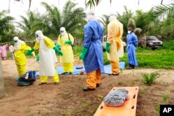 FILE - The wrapped remains of a new born child suspected of contracting the Ebola virus, lays on a stretcher as health workers, dressed in Ebola protective gear, move the body for burial in Dubreka, Guinea, June 19, 2015.