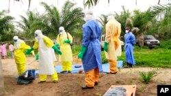 Des agents de la santé, vêtus d'équipement de protection contre le virus Ebola, transportent sur une civière les restes d'un enfant nouveau-né suspecté mort après avoir contracté l'épidémie, à Dubreka, Guinée, le 19 juin 2015